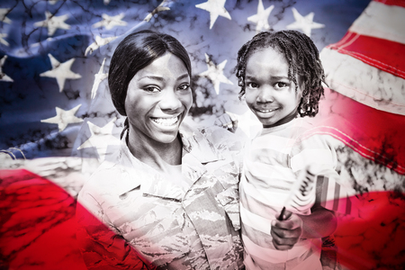 Full frame of American flag against portrait of happy mother carrying son at park