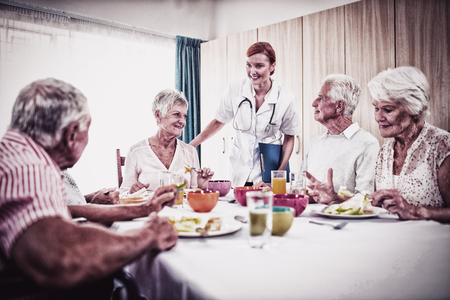 Pensioners at lunch with nurse in the retirement house Zdjęcie Seryjne