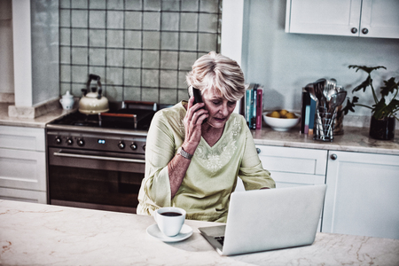 Senior woman talking on mobile phone while using laptop in kitchen Stock Photo