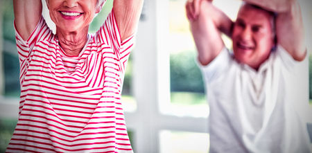 Happy senior couple performing stretching exercise at home Stock Photo