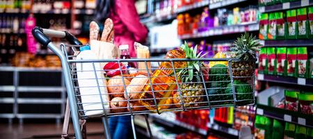Varios comestibles en el carrito de la compra en la sección de abarrotes del supermercado