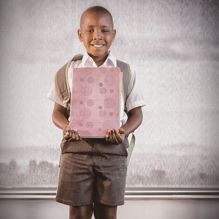 Happy schoolkid holding books and standing in classroom at school Imagens
