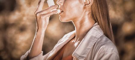 Woman using asthma inhaler in a park