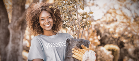 Portrait of female volunteer holding plant in park