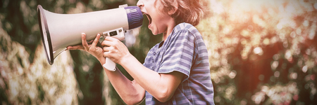 A little boy is screaming with a megaphone on a park Stock Photo