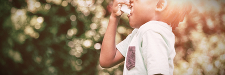 Boy using an asthma inhaler in the park Foto de archivo