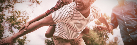Happy grandfather looking at man giving piggy backing to son with arms outstretched in yard Stock Photo