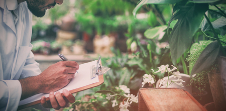 Side view of male scientist writing in clipboard while examining plants at greenhouse