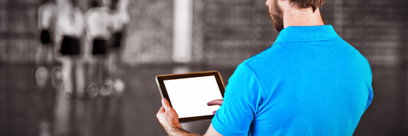 Male sports teacher using digital tablet in basketball court at school gym