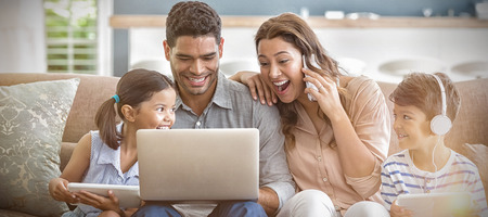 Parents and kids using laptop and digital tablet in living room at home