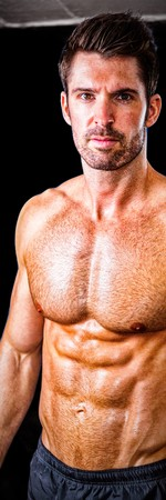 Portrait of shirtless male athlete standing in gym Stock Photo