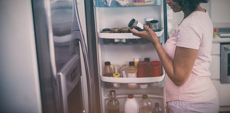 Woman removing bottle from refrigerator in kitchen at home Фото со стока