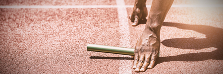Hands of athlete holding baton on running track Imagens