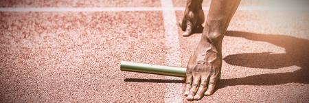 Manos de atleta sosteniendo el bastón en la pista de atletismo