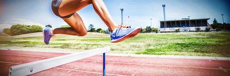 Female athlete jumping above the hurdle during the race Banque d'images