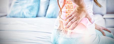 Compuesta digital de columna resaltada de mujer con dolor de espalda en casa Foto de archivo