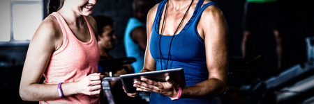 Smiling friends with digital tablet while standing in gym Stock Photo