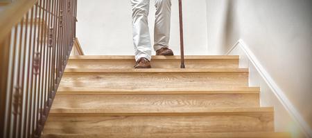 Senior man climbing downstairs with walking stick at home Stockfoto