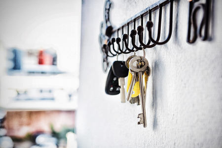 Close-up of various keys hanging on hook against wall