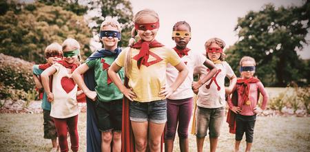 Children wearing superhero costume standing in the park