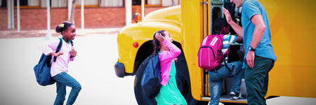 Teacher giving high five to kids while entering in bus at school 写真素材 - 119282157