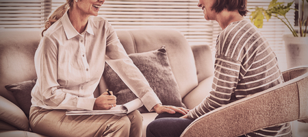 Happy therapist with patient on sofa at home