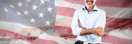 Portrait of businessman with arms crossed against close-up of an american flag