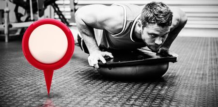 Close-up of red map location marker against muscular man using bosu ball