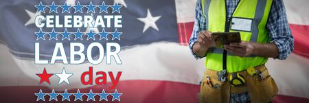 Mid-section of construction worker using tablet against full frame of american flag. USA Labor Day Concept Advertisement. USA Labor Day Concept Advertisement Reklamní fotografie