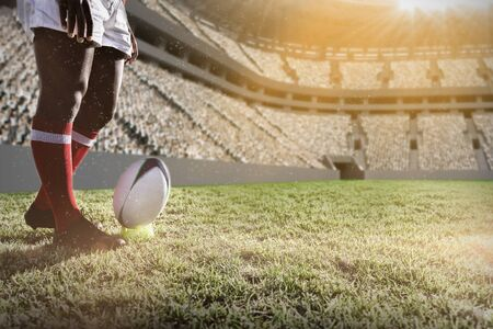 Rugby player preparing to kick the ball on field. against football stadium