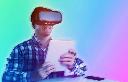 Male use virtual reality headset with digital tablet against turquoise and purple background