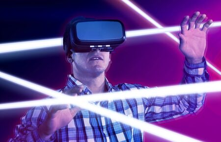 Male use virtual reality headset against turquoise and purple background