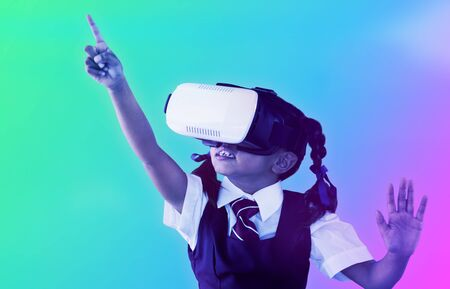 School girl pointing while using virtual reality headset against turquoise and purple background 스톡 콘텐츠