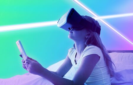 Girl using technology while wearing virtual reality simulator against turquoise and purple background