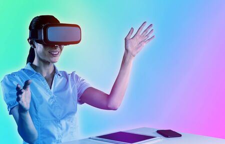 Female use virtual reality headset against turquoise and purple background Stock Photo