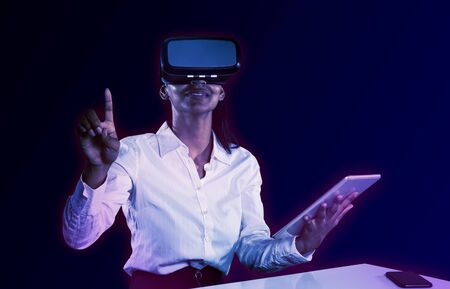 Female use virtual reality headset and digital tablet against gradient