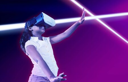 Girl gesturing while wearing virtual reality simulator against turquoise and purple background