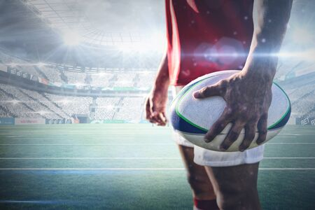 Rugby player holding rugby ball against stadium against sky