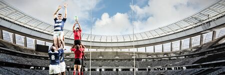 Rugby Players Playing Match against rugby goal post on a sunny day in the stadium Imagens