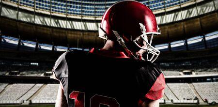 Giocatore di football americano nel casco che guarda di lato contro il palo della porta di rugby in una giornata di sole nello stadio