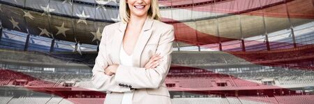 Portrait of confident businesswoman standing with arms crossed against close-up of an american flag Фото со стока