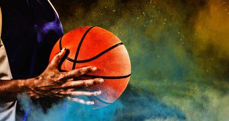 Tough female basketball player against splashing of yellow color powder