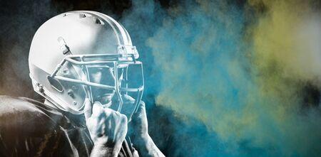 American Football Player against splashing of color powder