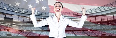 Successful businesswoman with clenched fists looking up against close-up of an american flag
