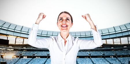 Successful businesswoman with clenched fists looking up against rugby stadium at dawn