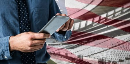 Mid-section of business man using smartphone against close-up of an american flag