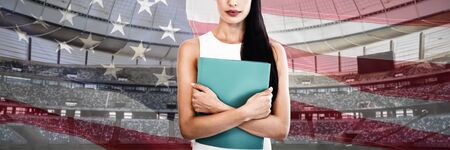 Portrait of businesswoman holding file against close-up of an american flag