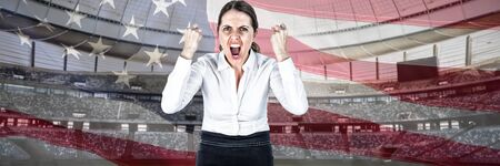 Portrait of screaming businesswoman clanching fists against close-up of an american flag 写真素材 - 129668520