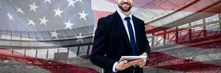 Portrait of smiling businessman holding digital tablet against close-up of an american flag Фото со стока