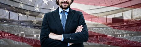 Portrait of businessman standing with arms crossed against close-up of an american flag Фото со стока